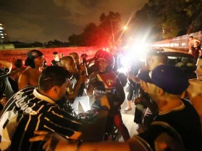 Policial com a camisa do São Paulo saca a arma na frente da torcida do Corinthians (Foto: Daniel Teixeira/Estadão Conteúdo)