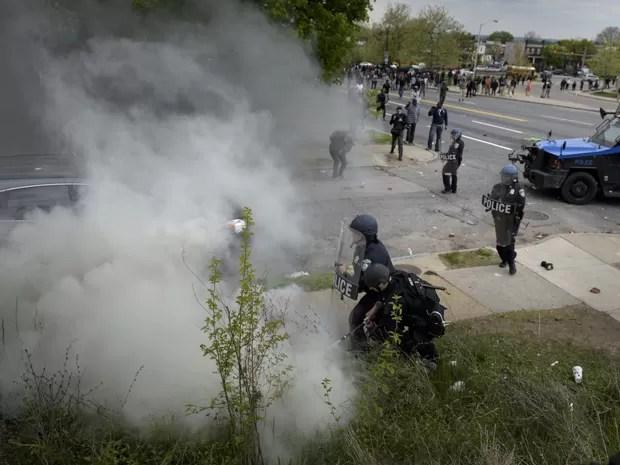 Policial tenta apagar chama causada por uma lata de gás lacrimogêneo durante confronto com manifestantes em Baltimore, na segunda (27) (Foto: AFP Photo/Brendan Smialowski)