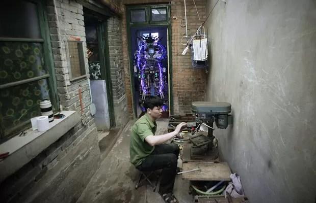 Chinês Tao Xingli, 37, constrói em casa um robô de 2 m de altura com restos de fio e metal (Foto: Suzie Wong/Reuters)