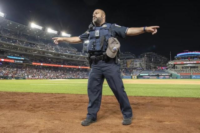 Policial organiza torcedores em estádio de beisebol, em Washington, após tiroteio do lado de fora em 17 de julho de 2021 — Foto: Brad Mills/ USA Today Sports/Reuters
