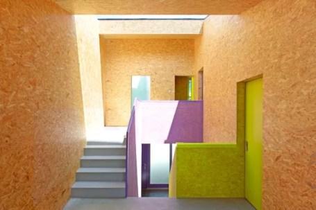 Em contraste com o piso de concreto, grandes placas de OSB foram tingidas de amarelo fluorescente e roxo, cores também aplicadas nos armários e portas. Na escada, a luminosidade da soleira ajuda a destacar as nuances ousadas (Foto: Thomas Jantscher e Nicolas Sedlatchek / Divulgação)