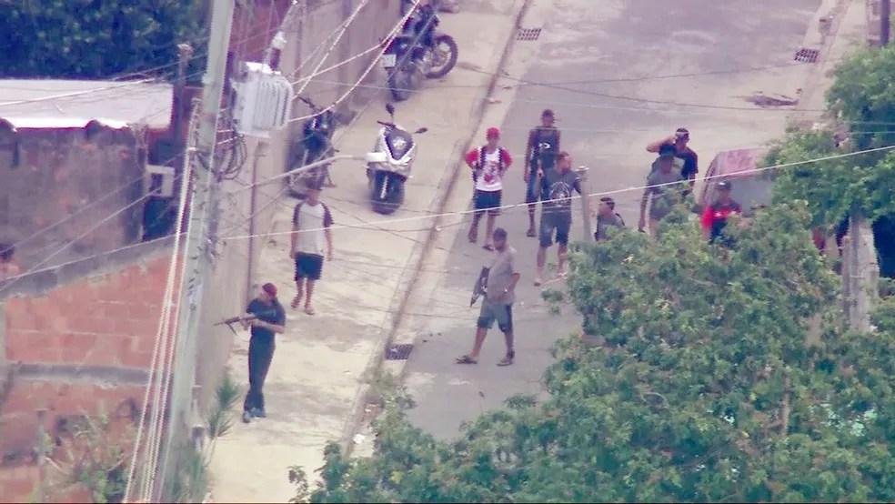 Homens armados com fuzis circulam no Chapadão — Foto: Reprodução/TV Globo