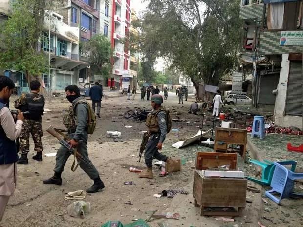 Forças de segurança afegãs inspecionam local de atentado suicida perto de banco, onde pessoas esperam em fila pelo recebimento de salário. (Foto: AP Photo)