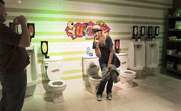 Turista tira foto perto de privadas e urinois que dispensam doces (Foto: Flávia Mantovani/G1)
