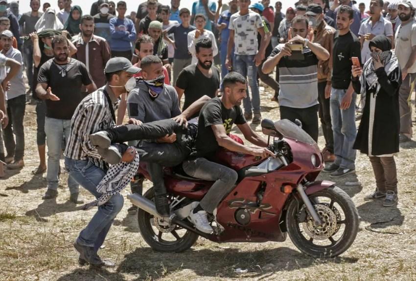 Palestinos colocam um companheiro ferido na garupa de uma moto para ser socorrido durante confronto com tropas israelenses perto da fronteira entre a Faixa de Gaza e Israel, no dia da abertura da Embaixada dos EUA em Jerusalém (Foto: Mahmud Hams/AFP)
