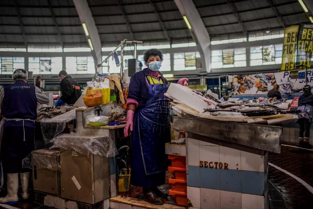 A vendedora de peixe Emilia Lomba, de 64 anos, posa para foto no mercado do Benfica em Lisboa, Portugal, durante a pandemia de COVID-19. Para Emilia, é um risco ir ao trabalho, porque ela encontra muitas pessoas todos os dias, mas precisa fazer isso para manter sua vida e suas contas pagas. É um sacrifício ir para o trabalho porque ela se sente mais segura em casa com sua família, mas, por outro lado, acha que tem sorte de poder estar na rua se comunicando com seus clientes e fornecendo peixe fresco — Foto: Patricia De Melo Moreira/AFP