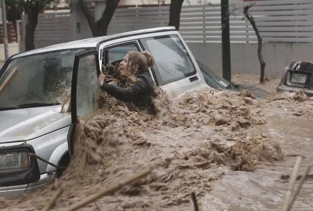 Mulher se esforça para deixar seu carro, com a força da água dificultando a saída no subúrbio ao norte de Atenas (Foto: John Kolesidis/Reuters)