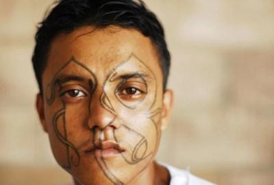 Membro da gangue Mara 18 exibe tatuagem na cadeia de Izalco (Foto: Ulises Rodriguez/Reuters)