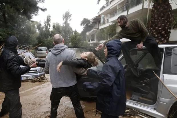 Pouco depois, o nível da água já desceu e permitiu que a mulher fosse carregada no socorro (Foto: John Kolesidis/Reuters)