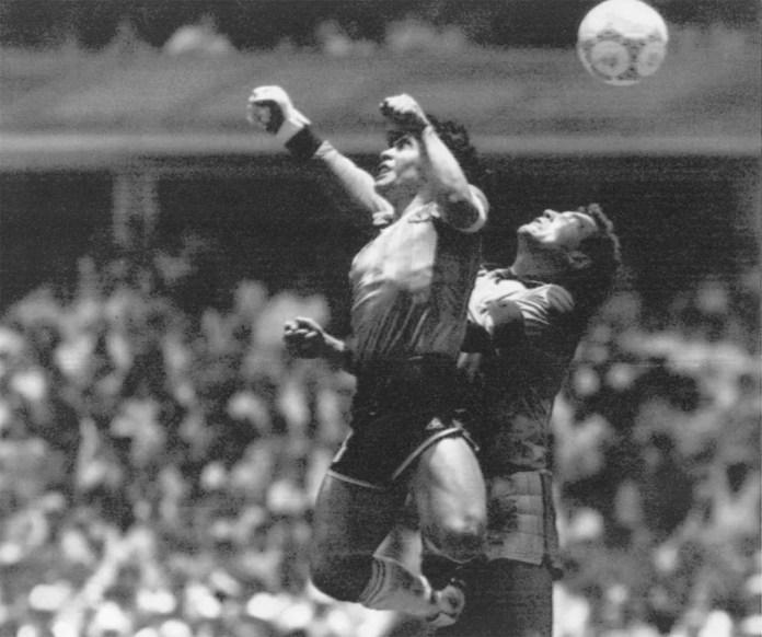 Maradona salta para dar um soco na bola e marcar um gol sobre a Inglaterra nas quartas-de-final da Copa do Mundo do México, em 1986. O episódio do gol ilegal validado pelo juiz ficou conhecido por 'A mão de Deus' — Foto: El Grafico via AP/Arquivo