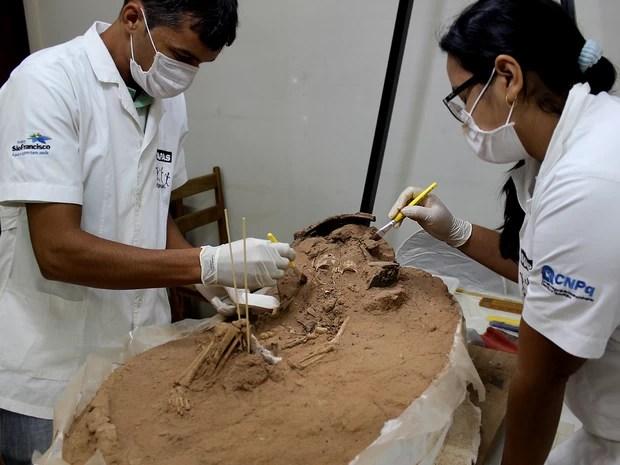 Arqueólogos trabalham em laboratório na escavação de uma criança enterrada há cerca de 3.500 anos no Piauí (Foto: Pedro Santiago/G1)
