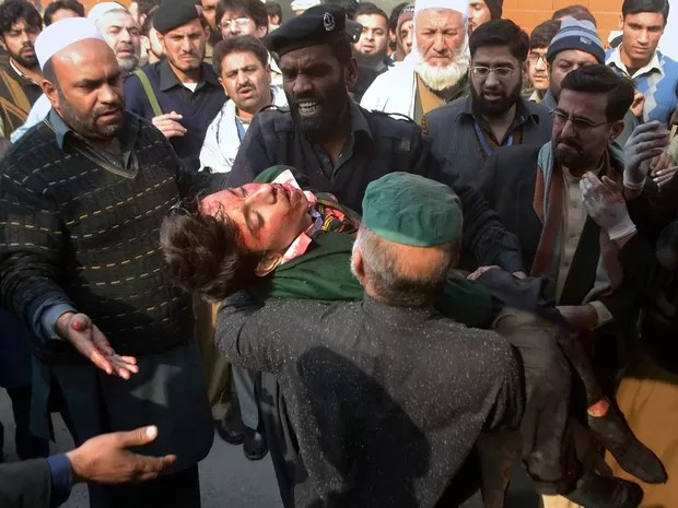 Feridos são retirados de escola que foi atacada pelo Talibã no Paquistão. Pelo menos 126 pessoas, a maioria crianças e adolescentes, foram mortos em ataque contra escola para filhos de militares em Peshawar, principal cidade do noroeste do país (Foto: Mohammad Sajjad/AP)