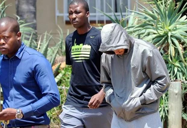 O corredor paralímpico Oscar Pistorius deixa delegacia rumo ao tribunal nesta quinta-feira (14) em Pretória, na África do Sul (Foto: AP)