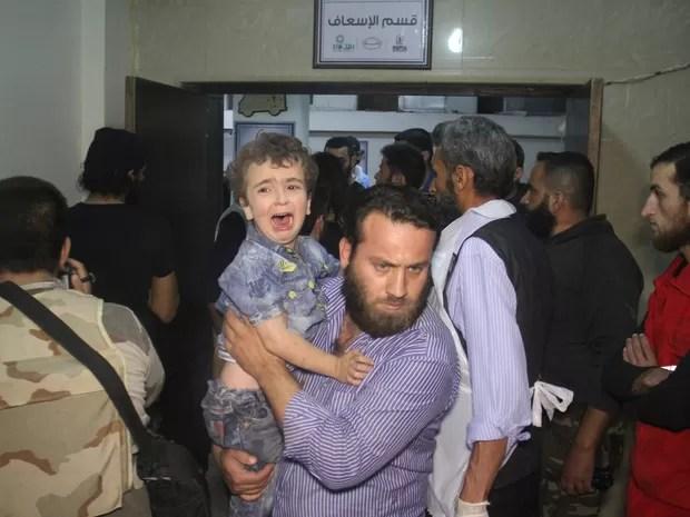 Sírio carrega criança em hospital após bombardeio russo em Idleb (Foto: Omar haj kadour/AFP)