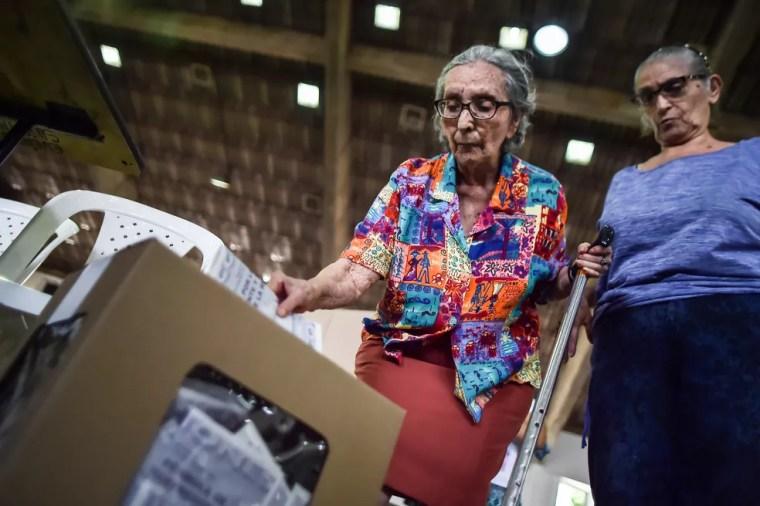 Mulher vota em primeiro turno de eleições presidenciais da Colômbia (Foto: Luis Robayo/AFP)