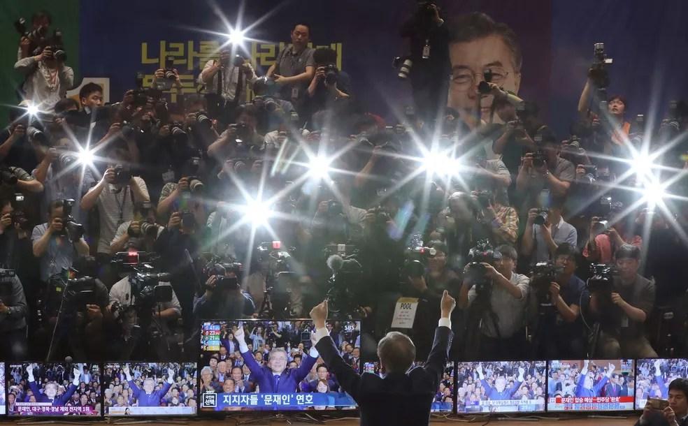 Moon Jae-in levanta os braços durante a transmissão dos resultados da eleição presidencial na Coreia do Sul  (Foto: Lee Jin-man/AP)