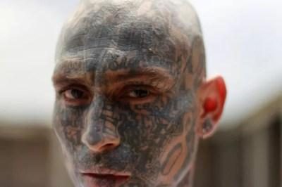 Outro membro da gangue Mara 18 mostra rosto todo tatuado na cadeia de Izalco (Foto: Ulises Rodriguez/Reuters)