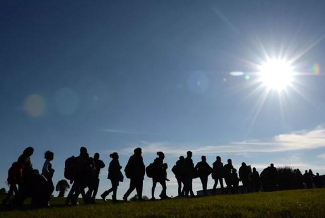 Migrantes são vistos andando da fronteira entre Alemanha e Áustria, em 2015, para o primeiro ponto de registro no território alemão perto da vila de Wegscheid. — Foto: Christof Stache/AFP
