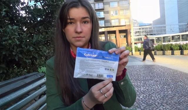 Usuária cadastrada, Maria Noel, em Montevidéu, mostra pacote de 5g de maconha legalizada (Foto: Carolina Dantas/G1)