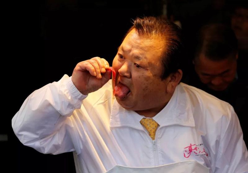 O presidente da Kiyomura Co, Kiyoshi Kimura, que controla a rede de restaurantes japonesa Sushi Zanmai, experimenta um pedaço do atum de 278 kg que ele arrematou por US$ 3,1 milhões em leilão no mercado de Toyosu, em Tóquio, neste sábado (5); valor superou recorde de 2013 — Foto: Kim Kyung-Hoon/Reuters