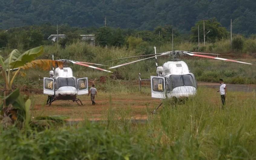 Dois helicópteros esperam perto da caverna (Foto: Sakchai Lalit / AP Photo)