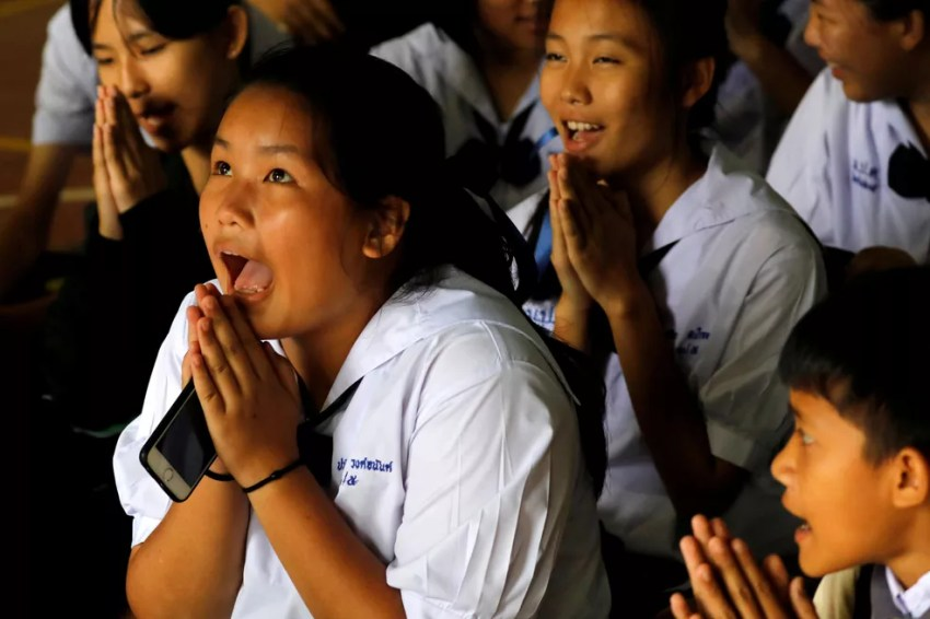 Colegas de escola de alguns dos meninos presos em caverna na Tailândia comemoram anúncio de mais um resgate nesta segunda-feira (9) (Foto: Tyrone Siu/ Reuters)