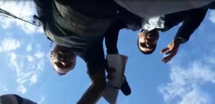 Policial e repórter brigam para pegar o celular no chão (Foto: Reprodução/TV TEM)