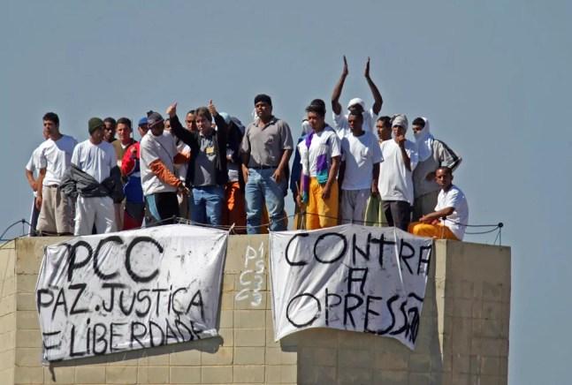 Presos fazem rebelião na Penitenciária de Junqueirópolis, em São Paulo, em 14 de maio de 2006. O motim começou às 7 da manhã, quando familiares entravam para a visita. Os rebelados subiram no telhado e prenderam faixas na caixa d´água com os dizeres: 'PCC, paz, justiça e liberdade' e 'Contra a Opressão' — Foto: Alex Silva/Estadão Conteúdo/Arquivo
