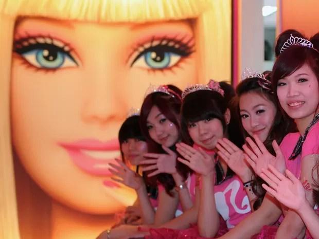 Garçonetes na frente de um cartaz Barbie durante a cerimônia de abertura de um restaurante temático  (Foto: AFP PHOTO / Sam Yeh)