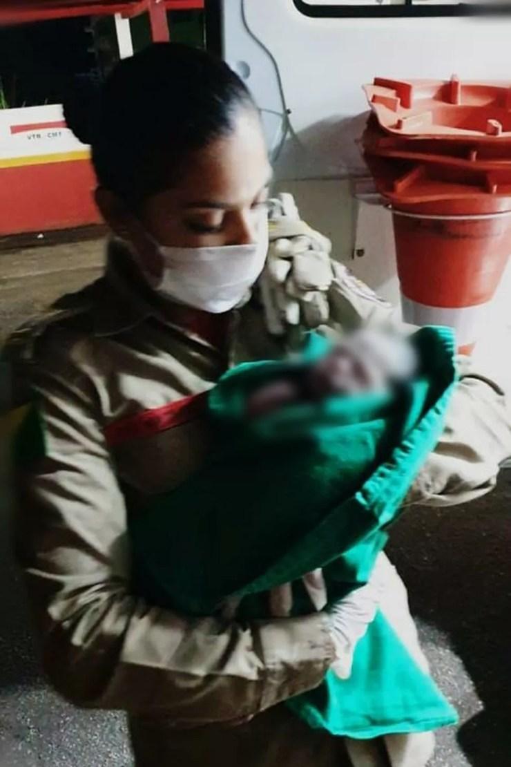 Katiuce segura a bebê após ter feito o parto da mãe  — Foto: Asscom/Bombeiros Acre