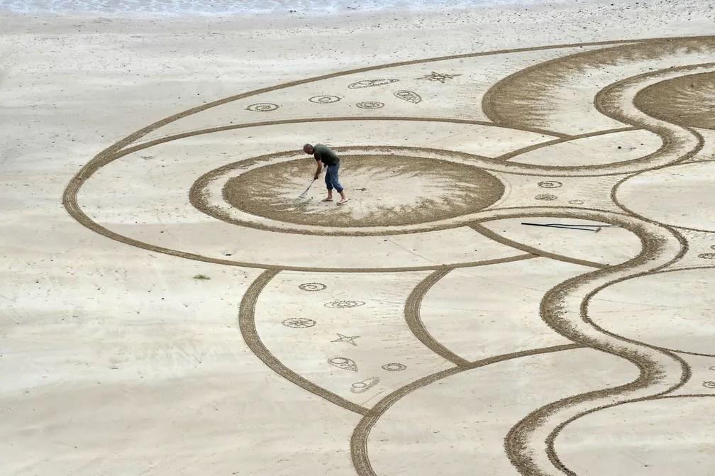 7 de junho - O artista de areia Marc Treanor trabalha em uma obra na Praia do Norte em Pembrokeshire, no País de Gales (Foto: Rebecca Naden/Reuters)