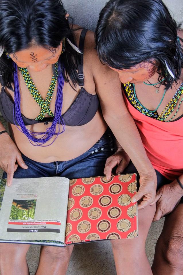 Mulheres Yanomami leem o livro 'Perisi - o fungo que as mulheres yanomami usam na cestaria' (Foto: Roberto Almeida / ISA)