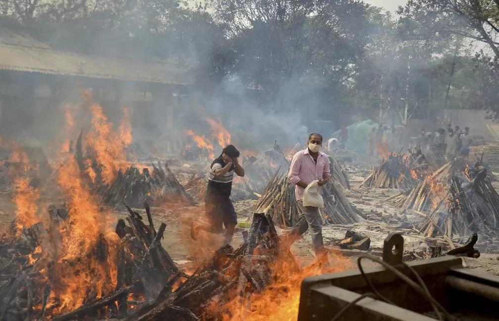 Parentes de uma vítima da Covid-19 caminham entre piras funerárias em crematório nos arredores de Nova Délhi, na Índia, em 29 de abril de 2021. Cremações em massa são feitas devido à disparada no número de mortes pelo país — Foto: Amit Sharma/AP