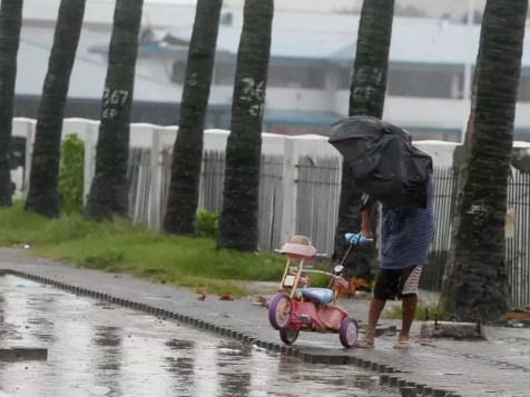 Homem segura triciclo infantil enquanto enfrenta ventos fortes durante a passagem de tufão nas Filipinas (Foto: AP Photo/Bullit Marquez)