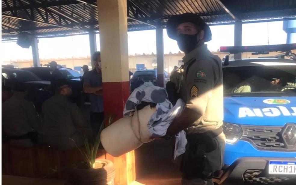 Momento em que policial chega com objetos encontrado em mata na base de comando em Cocalzinho de Goiás — Foto: Vitor Santana/G1 Goiás