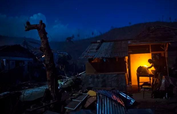 Um sobrevivente do tufão Haiyan cozinha em frente a sua destruída, na vila de Marabut, na Ilha Samar, nas Filipinas. O país tenta se reconstruir após a tempestade devastadora (Foto: David Guttenfelder/AP)