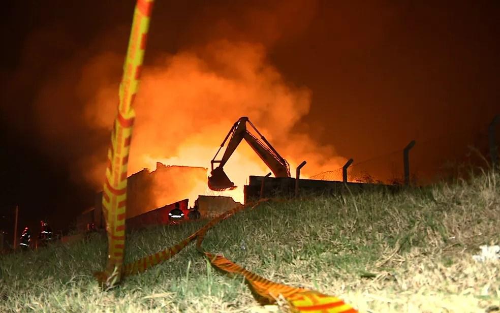 Retroescavadeira ajuda no combate ao incêndio no galpão de recicláveis de Hortolândia. (Foto: Reprodução/EPTV)