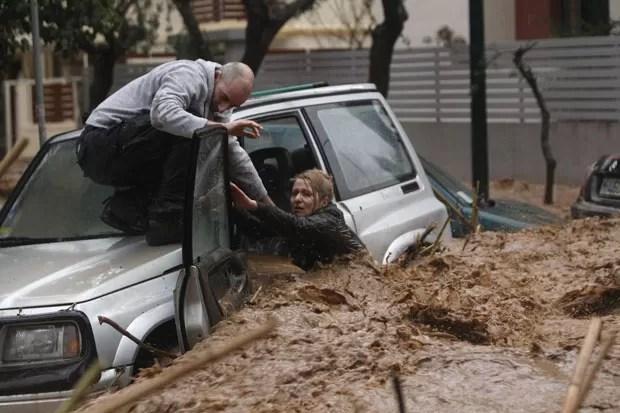 Morador de Chalandri socorre a motorista ilhada em seu carro (Foto: John Kolesidis/Reuters)