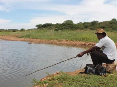 Agricultor tenta pescar em açude quase seco em Dormentes (Foto: Taisa Alencar / G1)