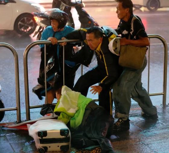Pessoas se seguram para ficar em pé durante a passagem de tufão em Taipé, Taiwan, neste domingo (30) (Foto: Tyrone Siu/Reuters)