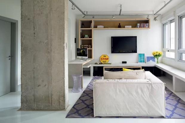 Em L, os bancos de cimento ladeiam o sofá da Carbono e o tapete da Square Foot. A placa Stop é da Coqueluche Presentes. Desenho do Superlimão Studio, o mobiliário feito de Wallplac compõe a área, que ainda serve de escritório (Foto: Edu Castello/Editora Globo)