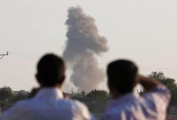 Curdos na Turquia observam explosão na cidade de Kobane, na Síria, nesta quarta-feira (8) (Foto: Lefteris Pitarakis/AP)