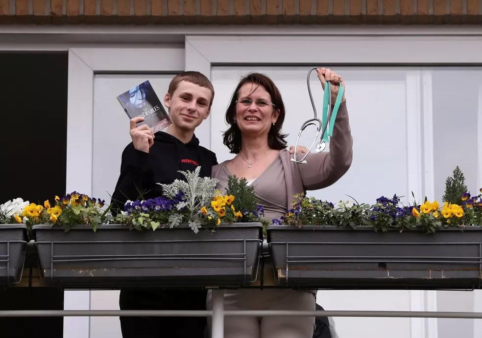 A residente Françoise e seu filho Denis posam na varanda de sua casa com objetos significativos para eles durante isolamento imposto pelo governo belga na tentativa de retardar o surto de doença por coronavírus (COVID-19) em Bruxelas, na Bélgica, em 19 de março — Foto:  Yves Herman/Reuters