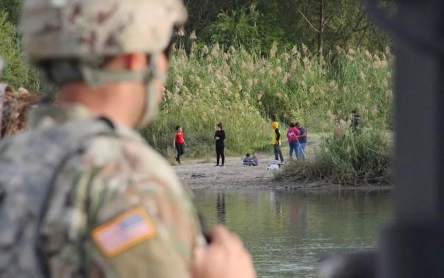 Um soldado do 19º Batalhão de Engenharia de Kentucky, em Laredo, no Texas, observa pessoas em Nuevo Laredo, México, do outro lado do Rio Grande, no domingo (18) — Foto: Thomas Watkins/AFP