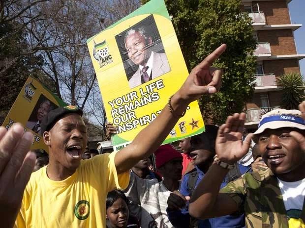 Membros do partido governista cantam fora do hospital onde Mandela está internado nesta quarta-feira (17) (Foto: Themba Hadebe/ AP)