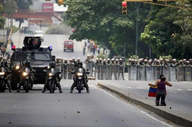 Manifestante com bandeira da Venezuela diante de policiais durante marcha da oposição nesta quinta-feira (20) em Caracas (Foto: REUTERS/Carlos Garcia Rawlins)