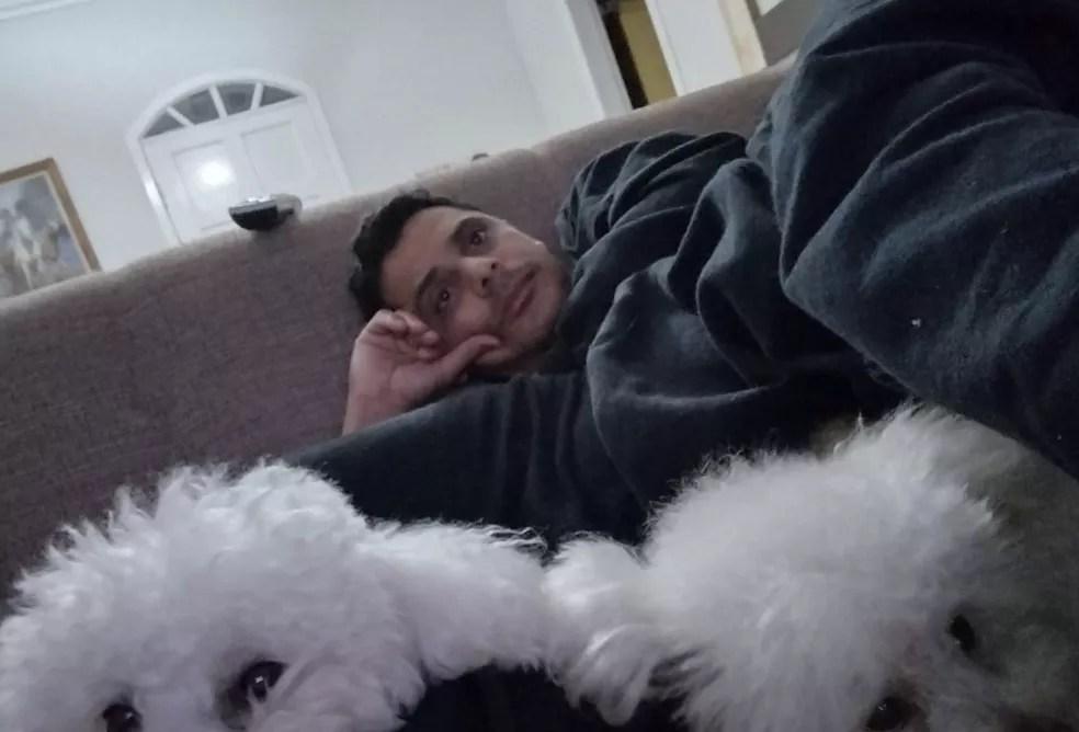 Denílson deitado no sofá da casa dele com suas cachorras se preparando para acompanhar as Olimpíadas. — Foto: Arquivo pessoal