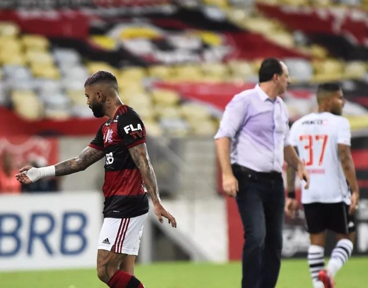 Gabigol abre os braços e reclama com Ceni, sem olhar para o treinador, que ouve de costas — Foto: André Durão