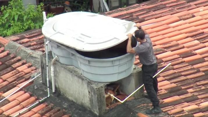 Agente vasculha caixa d'água na casa de Ronnie Lessa, na Barra — Foto: Reprodução/TV Globo