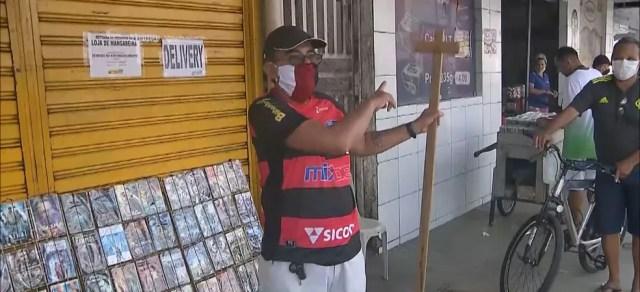 Pedagogo recorre a pedaço de madeira para manter distância em filas, em João Pessoa — Foto: TV Cabo Branco/Reprodução